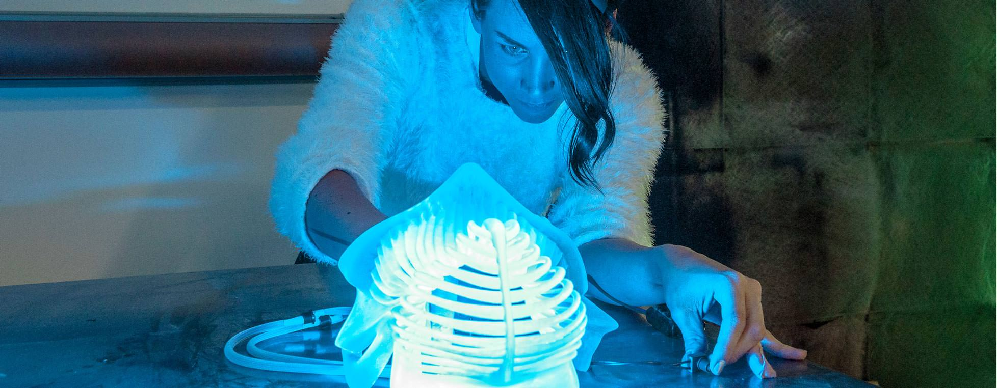 Image of a maker working on a blue, glowing model using Autodesk products.