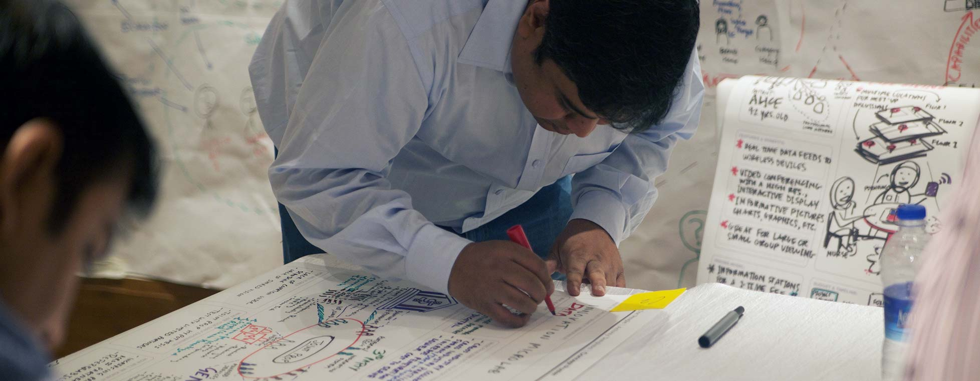 A Genpact team member sketches and writes to craft a visual presentation of a problem-solving concept during a Human-Centered Design work session.