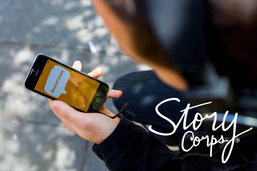 Photo of a person's hand holding a cell phone with the StoryCorps mobile app on the screen.