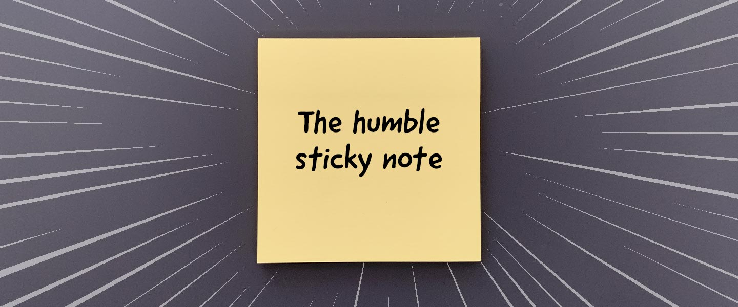 """Dark gray background with a yellow sticky note in the middle with the words """"The humble sticky note"""" written on it"""